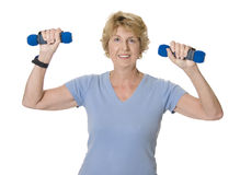 Active senior woman lifting blue weights Stock Image