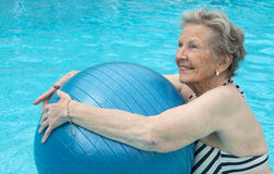 Active senior woman in the pool, doing exercises Stock Images