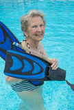 Active senior woman in the pool, doing exercises Stock Image