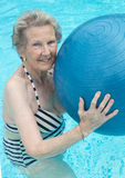 Active senior woman in the pool, doing exercises Royalty Free Stock Photography