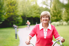 Active senior woman riding bike in a park Stock Photography