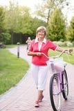 Active senior woman riding bike in a park Stock Photos