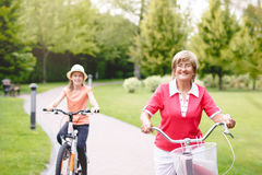 Active senior woman riding bike in a park. Happy active senior women riding bike with her grandaughter in park at summer royalty free stock images