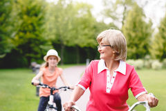 Active senior woman riding bike in a park. Happy active senior women riding bike with her grandaughter in park at summer stock photography