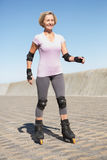 Active senior woman rollerblading on the pier Stock Photos