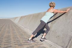 Active senior woman stretching on the pier Stock Image