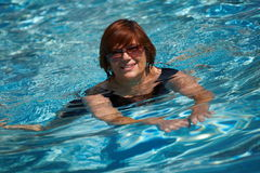 Active senior woman swimming. Happy active senior woman ( 60s ) swimming in pool at summer, smiling stock photography