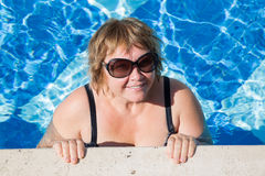 Active senior woman swimming in blue  pool water. Active pensionier woman swimming in blue water on vacation Royalty Free Stock Photography