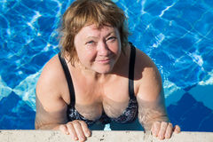 Active senior woman swimming in blue pool water. Active pensionier woman swimming in blue water on vacation Royalty Free Stock Photo