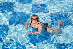 Active senior woman swimming in blue pool water Stock Photography