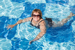 Active senior woman swimming in blue pool water. Active pensionier woman swimming in blue water on vacation Stock Images