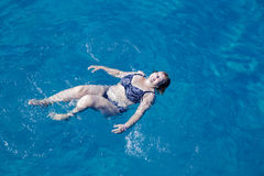 Active senior woman swimming in blue sea water. Active pensionier woman swimming in blue water on vacation Royalty Free Stock Images