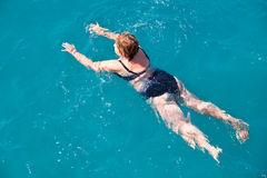 Active senior woman swimming in blue water Stock Photos