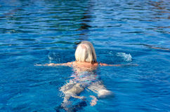 Active senior woman swimming in a pool Royalty Free Stock Image