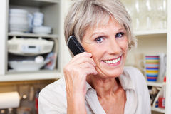 Active senior woman on the telephone. Active attractive senior woman with grey hair talking on the telephone and smilling while standing in her kitchen Stock Images