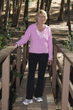 Active senior woman walking in a wood. Healthy elderly or mature woman walking across a bridge amongst trees, smiling happily, dressed in sporty clothes stock photography