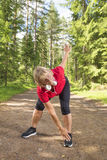 Active senior woman warming up before exercise stock photo