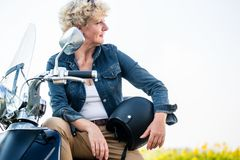 Active senior woman wearing a blue denim jacket while sitting on. Portrait of an active senior woman wearing a blue denim jacket while sitting on a motorcycle in Stock Photos