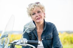 Active senior woman wearing a blue denim jacket while sitting on. Portrait of an active senior woman wearing a blue denim jacket while sitting on a motorcycle in Royalty Free Stock Photo
