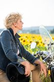 Active senior woman wearing a blue denim jacket while sitting on. Portrait of an active senior woman wearing a blue denim jacket while sitting on a motorcycle in Stock Photography