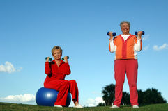 Active senior women. Two senior women with weights working out outdoors royalty free stock image