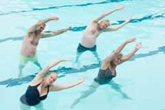 Active seniors exercising in swimming pool. High angle view of active seniors exercising in swimming pool Royalty Free Stock Images