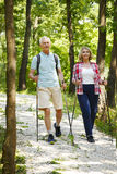 Active seniors. Full length portrait of active senior couple enjoying a nordic walk in the forest while old men and elderly women talking with each other Stock Photo