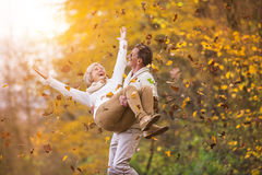 Active seniors having fun in nature. Active seniors having fun and playing with the leaves in autumn forest Royalty Free Stock Photos