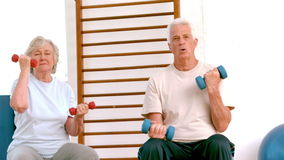 Active seniors lifting hand weights stock video footage