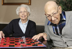 Active Seniors Playing Checkers. Active senior man and woman playing checkers stock images