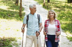 Active seniors. Portrait of senior couple enjoying a nordic walk. Active elderly women and men walking on the forest and smiling Stock Images
