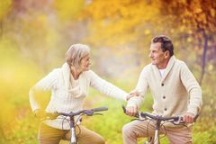 Active seniors riding bike. In autumn nature. They relax outdoor royalty free stock photos