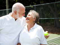 Active Seniors Romance. Active senior couple gets romantic on the tennis courts Royalty Free Stock Photo