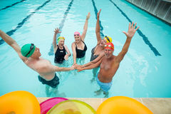 Active seniors stacking hands in pool. High angle view of active seniors stacking hands in pool royalty free stock photo
