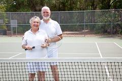 Active Seniors on Tennis Court. Portrait of active senior couple together on the tennis court Stock Photo