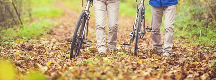 Active seniors walking with bike. Unrecognizable active seniors having walk with bike in autumn nature. They having romantic time outdoor Stock Photos