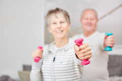Active seniors in working out. Active seniors couple in working out with weights at home Royalty Free Stock Photography