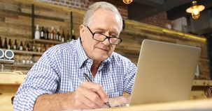 Senor man writing and using laptop in cafe 4k. Active senor man writing and using laptop in cafe 4k stock footage