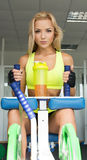 Active sexy blonde woman in sportswear sitting on the sports equipment. Gym. Sports nutrition. Amino acids. Sexy look. Royalty Free Stock Photo