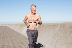 Active shirtless senior man jogging on the pier Stock Photos
