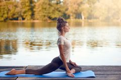 Active slender young woman exercising outdoors stock images
