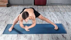Active slim male doing yoga professionally showing perfect stretching at studio high angle. Athletic focused yogi man enjoying exercise workout on mat full stock footage