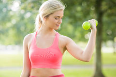 Active smiling blonde lifting dumbbells Royalty Free Stock Photography