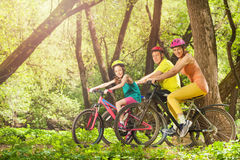 Active smiling family on bikes in the sunny forest stock photos