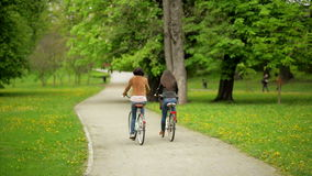 Active Smiling Female Friends with Dark Hair in Jackets and Jeans are Riding on the Bicycles. Back View of Two Pretty