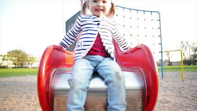 Active Smiling Little Girl with Ponytails Wearing Striped Jacket and Jeans is Enjoying Outdoors Game on Playground. Cute. Female Kid is Playing on Red Slide in stock video