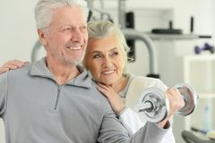 Active smiling senior couple exercising in gym stock images