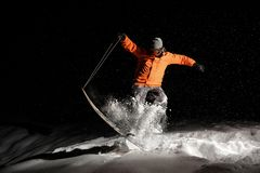 Active snowboarder in orange sportswear and mask jumping on a sn. Active snowboarder dressed in orange sportswear and mask jumping on a snowy hill at night royalty free stock photo