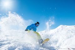 Active snowboarder. Riding down the hill in the mountains Royalty Free Stock Images