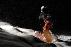 Active snowboarder riding down a snowy hill at night. Active snowboarder in black and orange sportswear riding down a snowy powder hill at black night royalty free stock photos